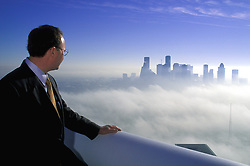 Businessman at high altitude with rooftop view of the downtown Houston, Texas skyline buildings in fog and low clouds.
