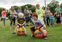 "Tyler Davignon yells ""GO"" for Braydon Malcolm and Marcus Gosselin as they start the obstacle course race at the Opechee Peanut Carnival on Thursday evening.  (Karen Bobotas/for the Laconia Daily Sun)"