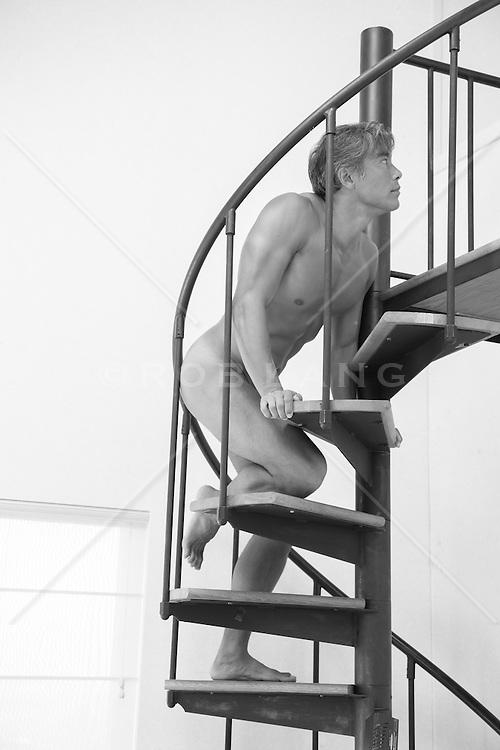 nude man climbing a spiral staircase