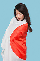 Patriotic young woman wrapped in Japanese flag over blue background