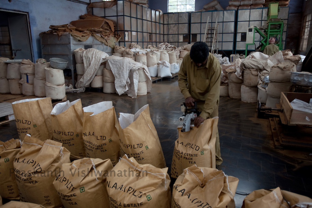A worker packs finished tea, at a tea factory in Conoor, India, on Friday May 21, 2010. Photographer: Prashanth Vishwanathan/Bloomberg News
