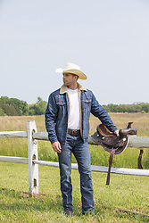 cowboy standing by a spilt rail fence with his saddle
