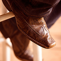 The cowboy boots of a musician rest on a stool while he plays his guitar