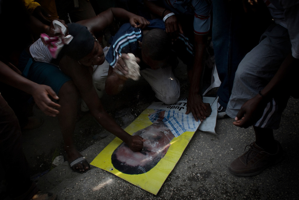 Supporters of presidential candidate Michel Martelly destroy a election poster of presidential candidate Jude Celestin during protests in Port-au-Prince, Haiti, Wednesday Dec. 8, 2010. Supporters of eliminated candidates protested after officials announced that government protege Jude Celestin and former first lady Mirlande Manigat would advance to a presidential runoff election.