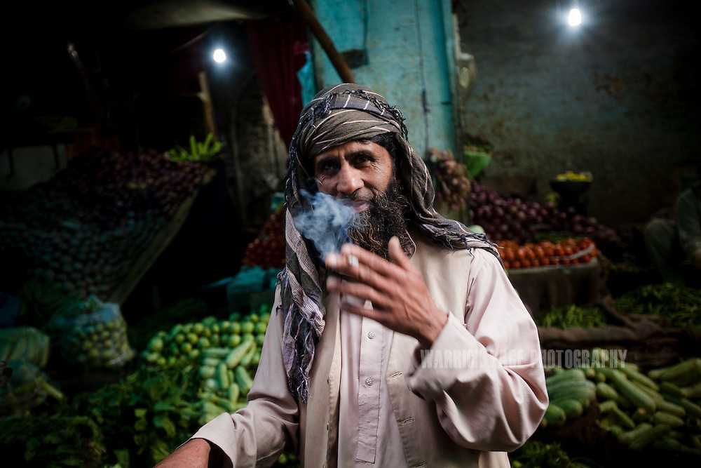 A fruit and vegetable vendor smokes outside his store on May 9, 2011 in Abbottabad, Pakistan. The town of Abbottabad became infamous after the US launched a midnight raid on a compound housing Osama bin Laden in the garrison town, on May 2, 2011. The operation, code-named Operation Neptune Spear, was launched from neighbouring Afghanistan and resulted in the killing of one of the world's most notorious terrorists and who claimed responsibility for the 9/11 attacks in the US. U.S. forces took bin Laden's body to Afghanistan for identification, then dumped it the Arabian Sea. Pakistan has since been widely suspected as having prior knowledge of his whereabouts as the compound was less than a kilometre from the country's biggest military academy. (Photo by Warrick Page)