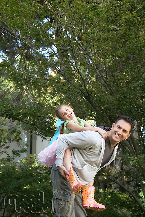 Father giving daughter piggy back ride in park