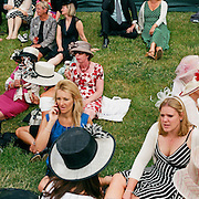 Spectators sit on a grassy embankment in the cheap enclosure at Royal Ascot, during the Royal Ascot race meeting. Royal Ascot. England, UK. June 16-20th, 2009. Photo Tim Clayton