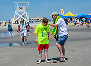 Chris Cronin, 35 gives Phil Cronin of Cape May a hand as he removes his sandals on the beach during the 11th annual 21 Down Beach Day Monday, July 15, 2019 at Schellenger Street beach in Wildwood, New Jersey. Every summer, the Wildwood Beach Patrol opens Lincoln Ave Beach for kids with down syndrome and their families for 21 Down Beach Day. Often, kids with down syndrome aren't comfortable in the ocean. Their parents can't just relax and watch them frolic. But on July 15th, the kids swim with seasoned Wildwood lifeguards on soft-top paddle boards. (Photo by William Thomas Cain / CAIN IMAGES)
