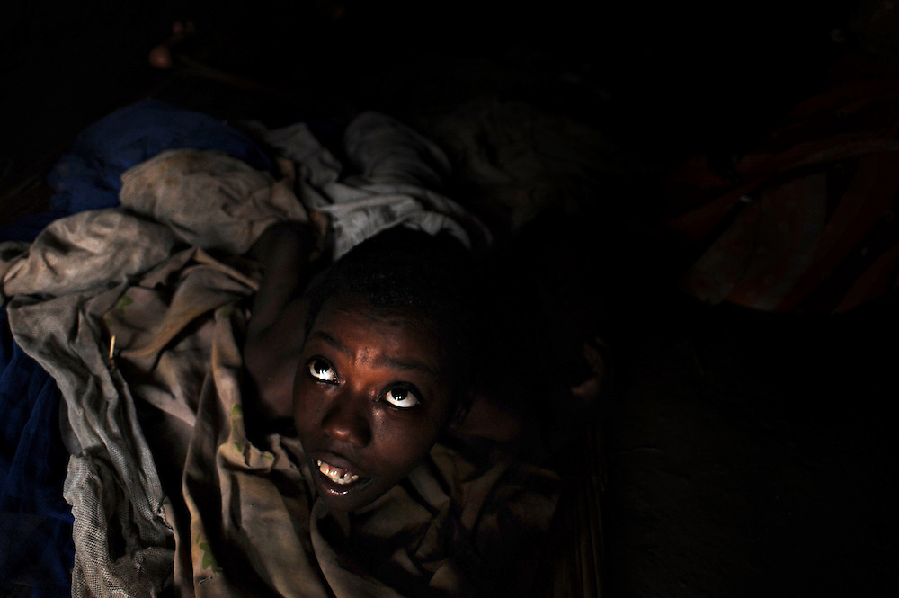 12-03-27   -- KITGUM, UGANDA --  Bedridden nodding disease victim Vicky Aciro, 14, in her mother's hut near Kitgum, Uganda on Tuesday, March 27.  While the Ugandan Government has opened nodding disease treatment centres at major northern hospitals, many in villages are unable to access the services due to transport costs and the limited mobility of the patient.  Aciro lives across the road from the Okidi Central Village Health Centre and is able to access services, but nurse Agnes Oroma says travelling doctors would be able to assist those living further away.  Some can't afford to go to the main hospital and some are stuck in villages which are not near transport. It's really difficult, says Oroma.   Photo by Daniel Hayduk