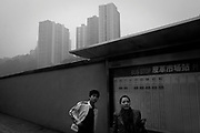 People wait for a bus at a bus stop in Chongqing. In Chongqing, a hilly city where one out of seven people uses public transportation every day.