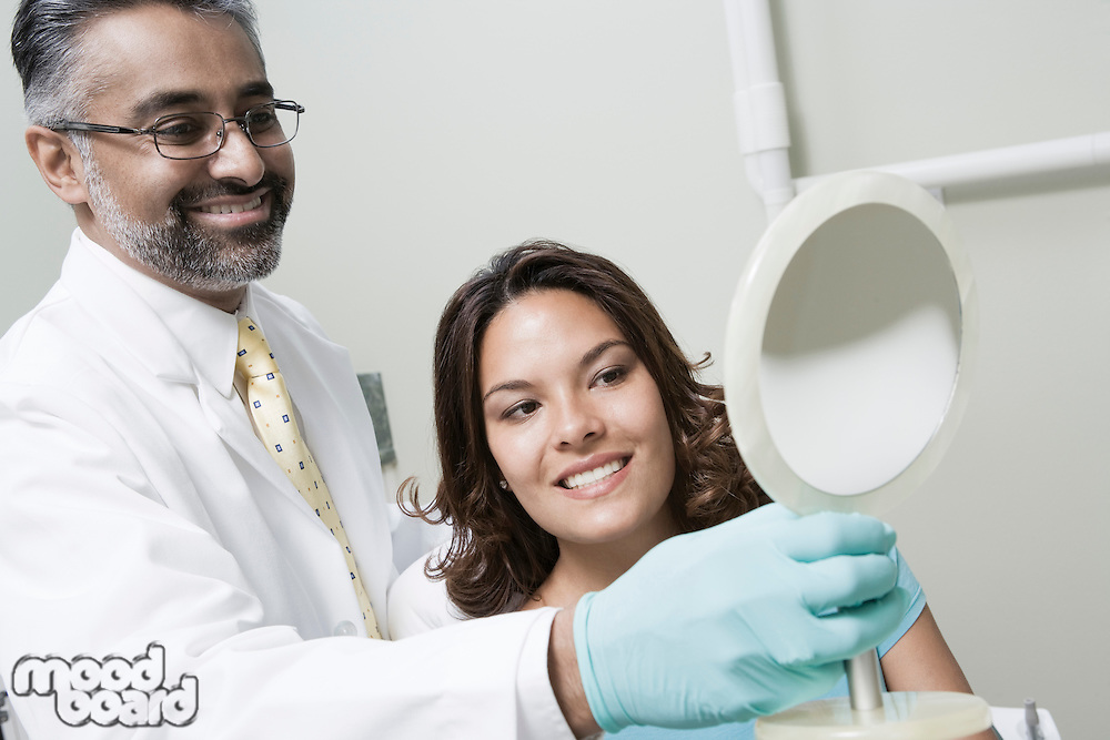 Dentist and patient using mirror