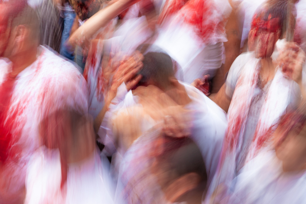 Shiite muslims, covered in their own blood, self-flagellating, commemorating the Day of Ashura, Nabatieh, Lebanon (November 14, 2013). Slow shutter speed.