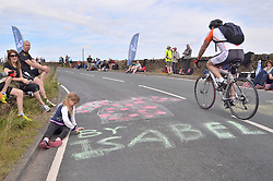 © Licensed to London News Pictures. 06/07/2014. Oxenhope nr Bradford, UK. Tour de France, 2nd Stage.A young graffiti artist signs her name in bold on the 3rd category climb of Oxenhope Moor a few hours before the race arrives. Photo credit : Ian Homer/LNP