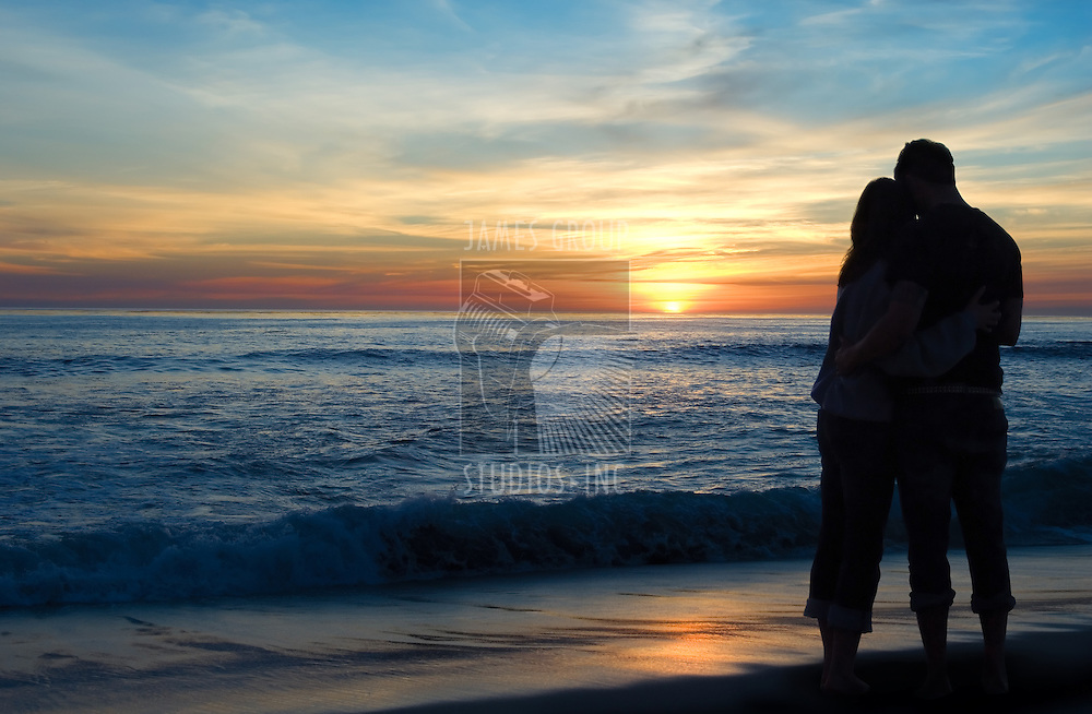Couple enjoying a romantic sunset over the ocean