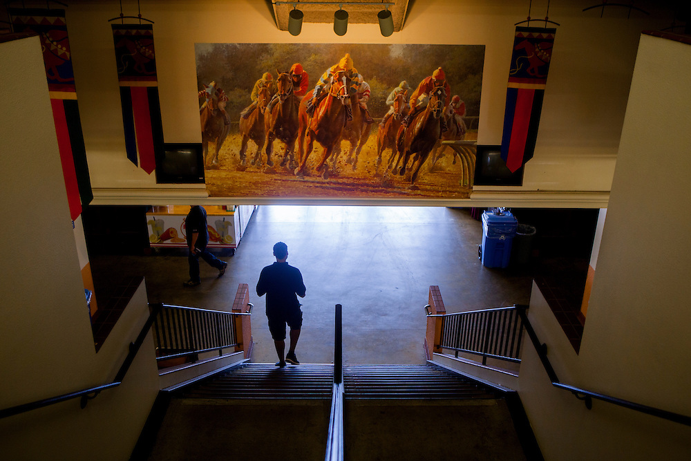 DEL MAR, CA - AUGUST 13, 2014:  A track goer walks beneath a painting of race horses on a dirt track at the Del Mar Thoroughbred Club. CREDIT: Sam Hodgson for The New York Times