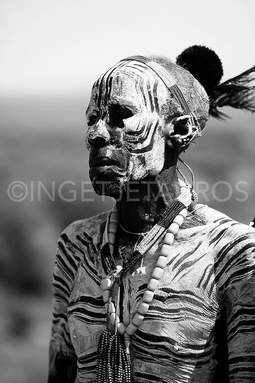 The Karo, which number only about 3,000 people, mainly live on the practice of flood retreat cultivationon the banks of the Omo River in southwestern Ethiopia.The Karo excel in face and body painting, practiced in preparation of their dances and ceremonies, they decorate their bodies, often imitating the spotted plumage of a guinea fowl. Feather plumes are inserted in their clay hair buns to complete the look. The clay hair bun can take up to three days to construct and is usually re-made every three to six months. Their painted facemasks are spectacular. Karo women scarify their chests to beautify themselves. Scars are cut with a knife and ash is rubbed to produce a raised welt.<br /> Being the smallest tribe I the area, this group obviously struggles which direct threats from nearby tribes that have more gun power, greater numbers, and likely coalitions with one another.