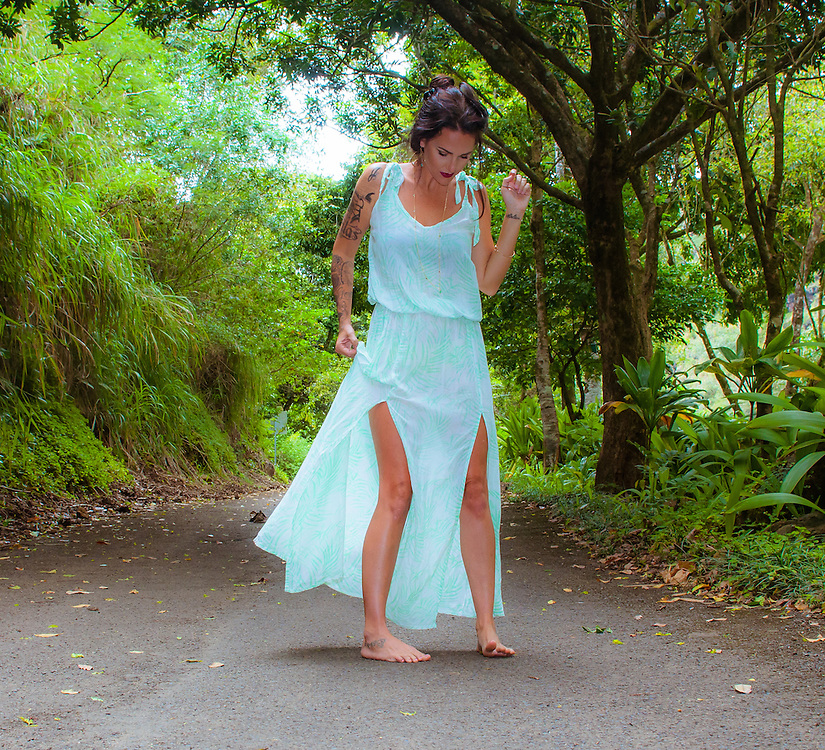 Woman on the bike path on North Shore of Oahu in Hawaii wearing a light blue Tiare Hawaii Dress. <br />