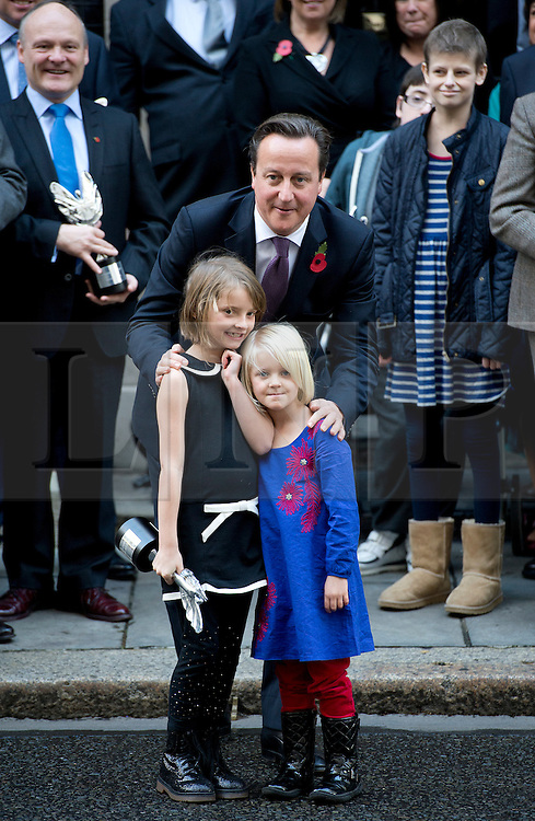 © London News Pictures. 30/10/2012. London, UK.  British Prime Minister David Cameron poses with sisters Ramona Gibbs (7) Trixie Gibbs (5) and other award winners during a photo call with the winners of the Pride of Britain awards in front of 10 Downing Street on October 30, 2012. Ramona pushed her sister Trixie to safety from an oncoming car but sustained serious injuries herself.  Photo credit: Ben Cawthra/LNP..