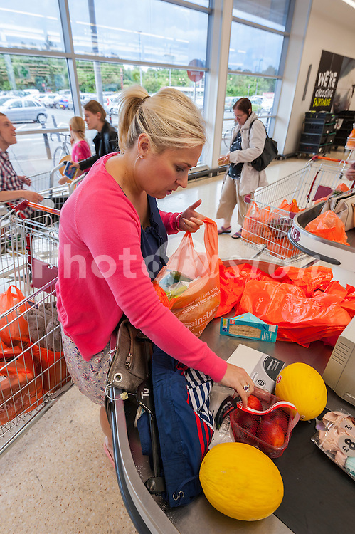 A woman packing her shopping in a Sainsburys supermarket in the Uk