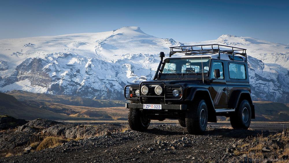 A Land Rover Defender by river Markarfljot. In background is Husadalur in Thorsmork and Eyjafjallajokull Glacier.<br /> <br /> Land Rover Defender vi&eth; Markarflj&oacute;t, H&uacute;sadalur og Eyjafjallaj&ouml;kull &iacute; baks&yacute;n.