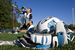 29 September 2007: North Carolina Tar Heels men's lacrosse member Colin Sherwood with a helmet and glove in the foreground during a practice on the turf field in Chapel Hill, NC.
