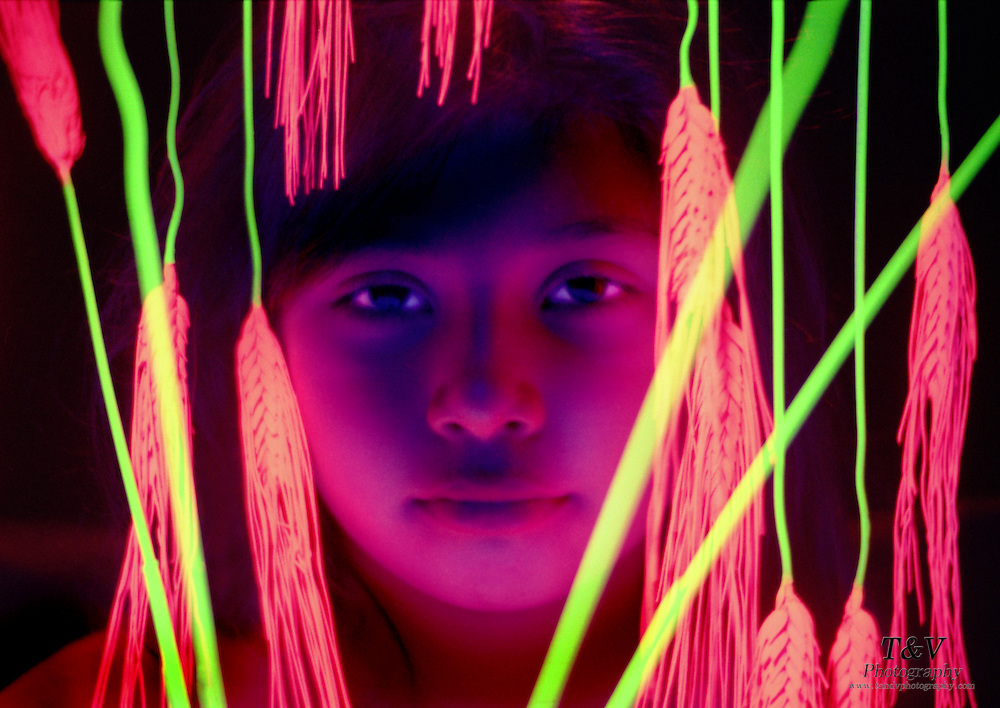 Young girl looking through glowing wheat.Black light