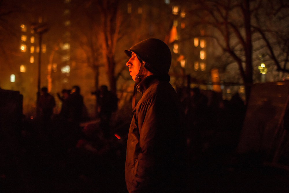 KIEV, UKRAINE - FEBRUARY 20: An anti-government protester stands watch at front-line barricades on Instytutska Street, near Independence Square, on February 20, 2014 in Kiev, Ukraine. After several weeks of calm, violence has again flared between anti-government protesters and police, with dozens killed. (Photo by Brendan Hoffman/Getty Images) *** Local Caption ***