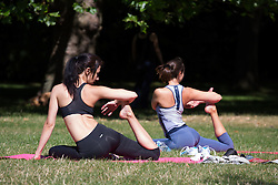 Image ©Licensed to i-Images Picture Agency. 16/07/2014. London, United Kingdom. Bright and hot day with max. temperatures of 27ºC. Girls strech themselves in Regens' park this morning in a bright and hot day. Regent\'s Park. Picture by Daniel Leal-Olivas / i-Images