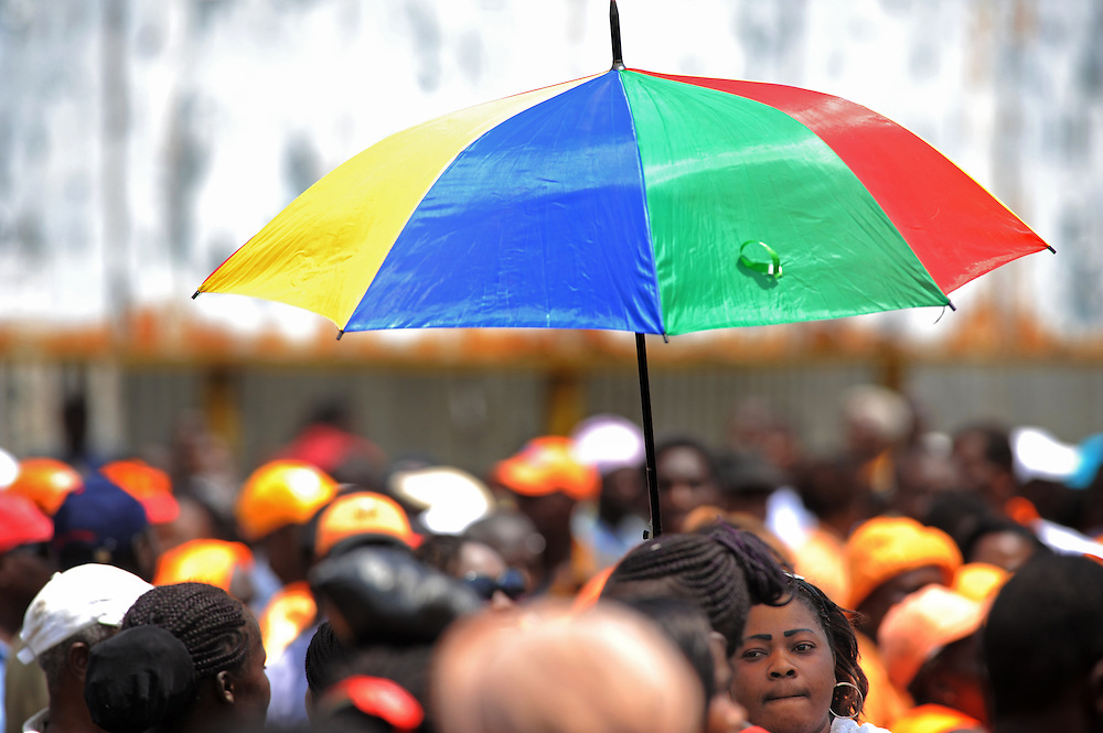LOME, TOGO  13-02-16   -  A woman holds an umbrella as several thousand opposition supporters marched peacefully through the streets of Lome on Saturday, February 16.  Photo by Daniel Hayduk