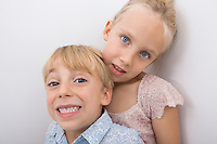 Portrait of happy brother with sister over gray background