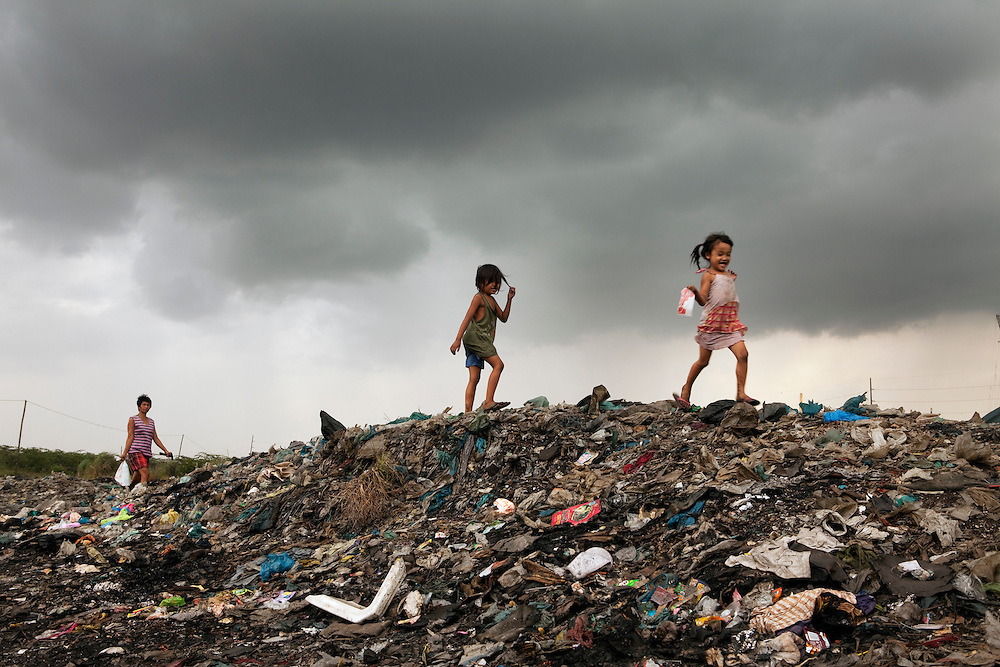 Kids play on the garbage dump close to their home in Manila. their family makes a living from scavenging and they have recently been moved by the company that manages the garbage dump. Slum area in Manila, Philippines
