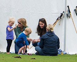 © Licensed to London News Pictures. 14/06/2015. Prince George of Cambridge and his mother Catherine Duchess of Cambridge talking to Autumn Phillips  and Daughter Savannah Phillips, with Zara Phillips (far right) . British Royals attend a charity Polo match in Tetbury,  Gloucestershire, UK. Photo credit: Ben Cawthra/LNP