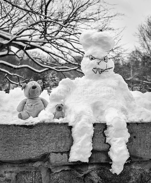 A little girl poised her stuffed animals alongside this snowman for a picture.