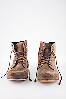 Pair of brown boots with untied laces over white background