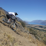 Andrew Paisley from Dunedin in action during the New Zealand South Island Downhill Cup Mountain Bike series held on The Remarkables face with a stunning backdrop of the Wakatipu Basin. 150 riders took part in the two day event. Queenstown, Otago, New Zealand. 9th January 2012. Photo Tim Clayton