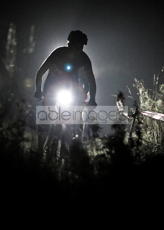 Cyclists Racing at Night Illuminated by the Lights on their Bicycles