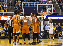 Feb 20, 2017; Morgantown, WV, USA; Texas Longhorns players huddle while West Virginia Mountaineers guard Jevon Carter (2) shoots a foul shot after a technical foul was called during the first half at WVU Coliseum. Mandatory Credit: Ben Queen-USA TODAY Sports
