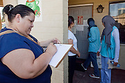 20 JUNE 2009 - PHOENIX, AZ: Mireya Renteria, from Phoenix, signs in at the walk in clinic at the Cultural Cup. The walk in clinic at the Cultural Cup Food Bank started two years ago when Cultural Cup founder Zarinah Awad wanted to expand the food bank's outreach and provide basic medical care for the people who use the food bank. The clinic sees, on average, 7 - 11 patients a week. Awad said that as the economy has worsened since the clinic opened and demand has steadily increased. She attributes the growth to people losing their jobs and health insurance. The clinic is staffed by volunteers both in the office and medical staff. Adults are seen every Saturday. Children are seen one Saturday a month, when a pediatrician comes in. Awad, a Moslem, said the food bank and clinic are rooted in the Moslem tradition of Zakat or Alms Giving, the giving of a small percentage of one's income to charity which is one of the Five Pillars of Islam.   PHOTO BY JACK KURTZ