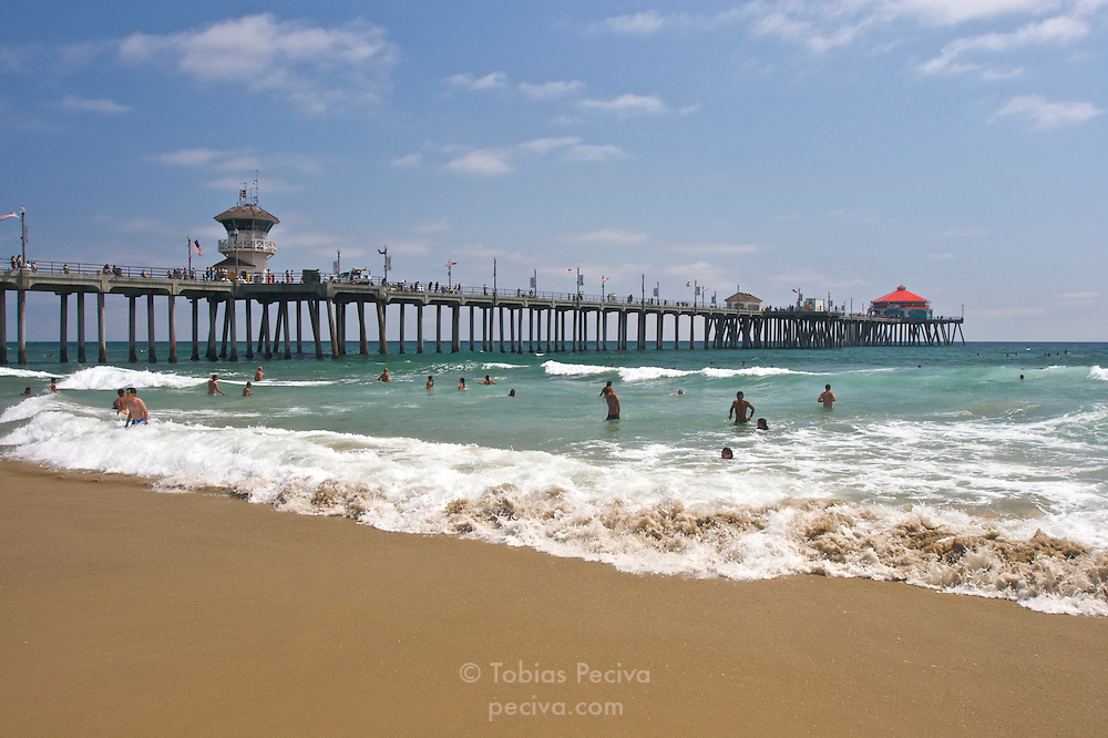 Swimmers enjoying Pacific Ocean waves near the Huntington Beach Pier in Huntington Beach, California.