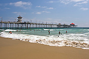 Swimmers enjoying Pacific Ocean waves near the Huntington Beach Pier in Huntington Beach, California.