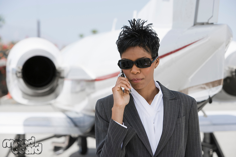 Mid-adult African-American businesswoman standing in front of private plane and talking on phone.