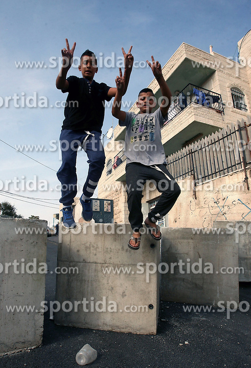 19.10.2015, Jerusalem, ISR, Gewalt zwischen Pal&auml;stinensern und Israelis, im Bild Kontrollen der Israelischen Sicherheitskr&auml;fte im Pal&auml;stinenser Gebiet // Palestinian boys jump over cement blocks at a newly erected checkpoint in Jerusalem's neighborhood of Jabal al-Mokaber on October 19, 2015. Israeli police began erecting a wall in east Jerusalem to protect a Jewish neighbourhood subject to firebomb and stone attacks launched from an adjacent Palestinian village, Israel on 2015/10/19. EXPA Pictures &copy; 2015, PhotoCredit: EXPA/ APAimages/ Mahfouz Abu Turk<br /> <br /> *****ATTENTION - for AUT, GER, SUI, ITA, POL, CRO, SRB only*****