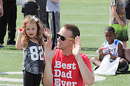 Lilah, 4, and Brooks Enders wave their hands to the music during the All Pro Dad Father & Kids NFL Experience at Welcome Stadium, Saturday, June 18, 2016.