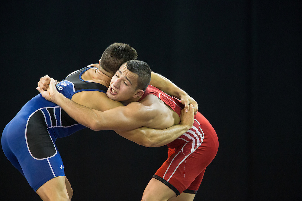 Maximiliano Prudenzano of Argentina (R) grapples with Alvis Almendra of Oanama in their quarter final bout in the 75kg class of the men's greco-roman wrestling  at the 2015 Pan American Games in Toronto, Canada, July 15,  2015.  AFP PHOTO/GEOFF ROBINS
