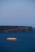 Sydney Harbour Ferry passing North Head at dusk in a blur of lights, Australia
