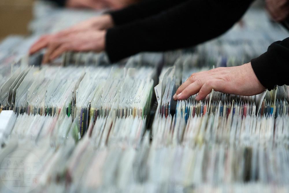 Vingers van bezoekers van de Verzamelaarsjaarbeurs in de Jaarbeurs in Utrecht bladeren door bakken met allerlei LP's.<br /> <br /> Fingers of visitors of the collectors fair are searching through record albums.