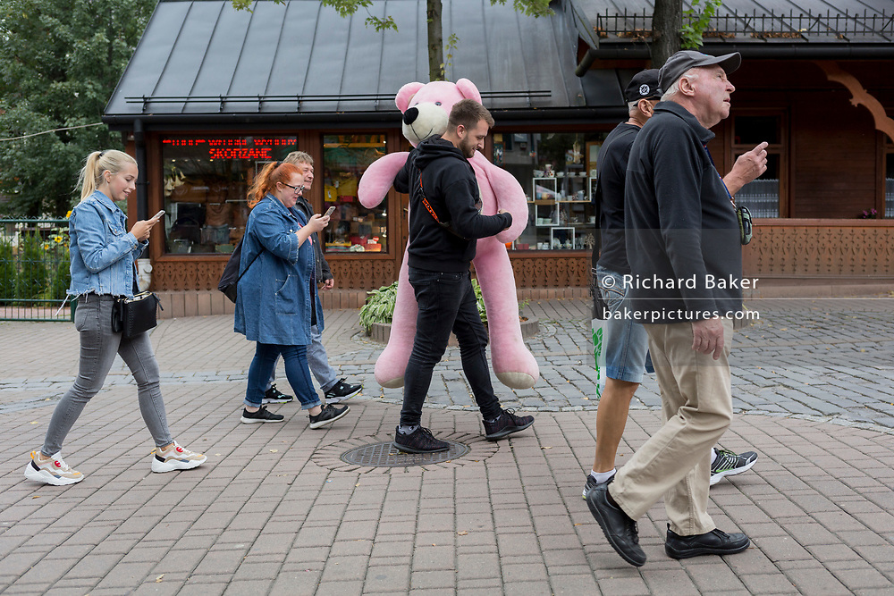 A Polish man carries pink fairground bear along Krupowki Street, on 16th September 2019, in Zakopane, Malopolska, Poland.