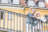 Happy middle-aged couple taking selfie through digital camera against building