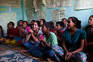 Sarawati Regmi (center, white), 11, attends a club meeting at the Kishuri Sachetana Child Club in their activity center in Thahuri Tole, Chhinchu, Surkhet district, Western Nepal, on 1st July 2012. Sarawati's ambition is to run an NGO. 16-year-old Bhawani Regmi (in grey/pink) who is the president of the district level child forum, 11-year-old  Sarawati Regmi (in white), and 10-year-old Ganga Regmi (in pink) are daughters of pandit (Hindu priest) Dharma Raj Regmi who is one of the 3 priests who have agreed to stop solemnizing child marriages. These Child Clubs, supported by the government, Save the Children and their local partner NGO Safer Society, advocate for child rights and against child marriages and use peer support and education to end child marriages and raise awareness. Photo by Suzanne Lee for Save The Children UK