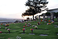 The sun sets at Queen of Heaven Cemetery. In a touching final celebration of All Soul's Day on Saturday night, hundreds of congregants came to Queen of Heaven in Salinas to attend mass, offer their prayers, and as dusk fell, participate in a candlelight procession.  Friends and family members sat by the graves of loved ones, many of which were decorated with traditional Day of the Dead marigolds, photographs of the departed, and things that were their favorites in life.